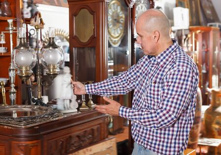 Adult male carefully examining antiques in store