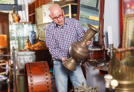 focused senoir man visiting shop of antique goods in search of interesting objects Stock Photo