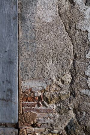 Texture of old damaged stone wall with closed wooden shutters