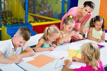 Glückliche frohe Kinder, die zusammen mit dem Tutor in der Hobbygruppe drinnen zeichnen
