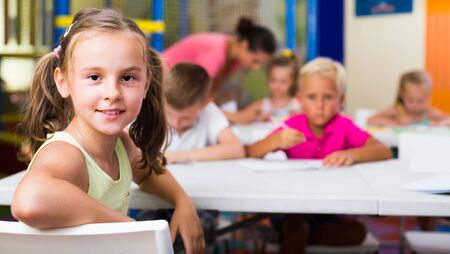 Portrait of cheerful smiling  little school girl sitting at lesson