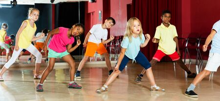 Focused kids studying modern style dance in class indoors Stock Photo