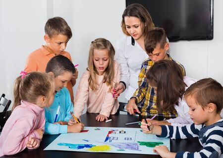 Happy children with teacher drawing together in classroom