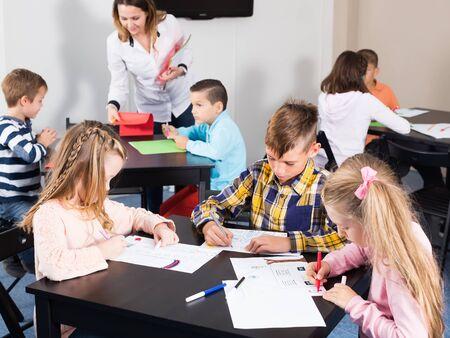Lachende leraar en kinderen in de basisschoolleeftijd tekenen in de klas Stockfoto