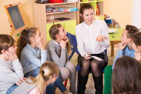 Lächelnde attraktive Kinder im Grundschulalter sitzen und hören Lehrer in der Klasse