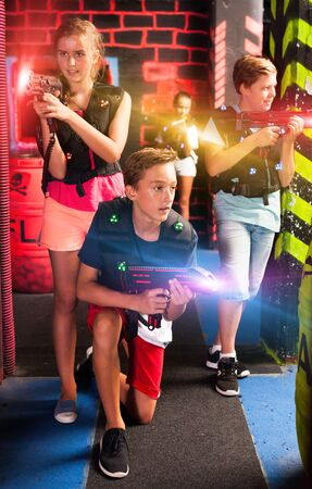Modern teen girls and boys with laser pistols playing laser tag on dark labyrinth