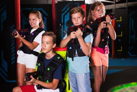 Cheerful teen girls and boys with laser pistols posing together in dark laser tag labyrinth Фото со стока