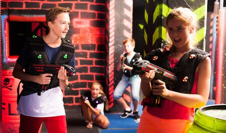 Modern teen girls and boys with laser pistols playing laser tag on dark labyrinth Фото со стока