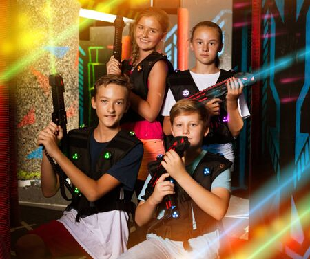 Group portrait of happy teenagers with laser guns having fun on dark lasertag arena Фото со стока