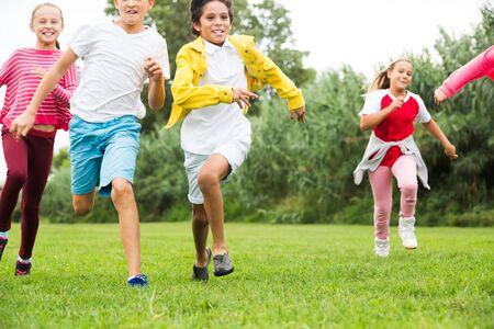 I bambini felici stanno facendo jogging insieme nel parco e si divertono Archivio Fotografico