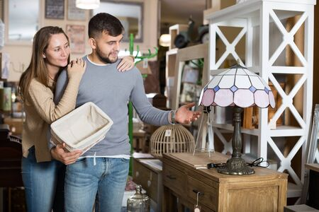 Attractive girl with boyfriend visiting salon of antique furniture in search of table lamp