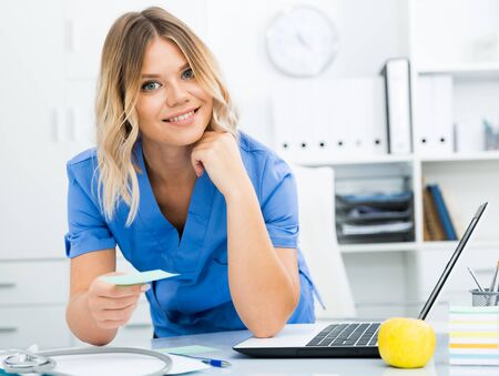 Kindly woman in doctors uniform greets visitors at modern office