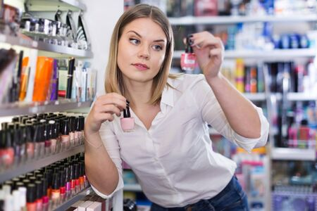 Young woman looking for new stylish color of a nail varnish in a cosmetic shop