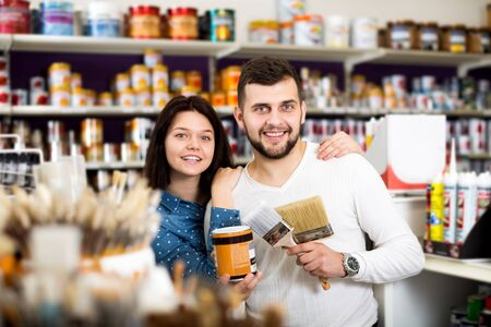 Cheerful young couple examining various painting brushes in paint supplies store