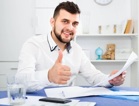 Smiling cheerful young man signing profitable financial agreement at home