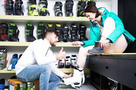 Positive young couple choosing ski boots for girl in sport goods store. Focus on girl Stock fotó