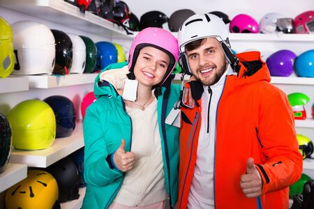 Friendly positive  man and woman standing with purchased ski equipment in shop