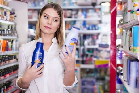 Young concentrated woman looking for a haircare cosmetics in a shop Фото со стока