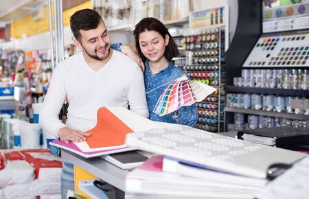 Smiling couple examining various decorative materials in the paint supplies store. Focus on woman Imagens
