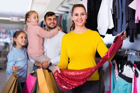 Young  cheerful positive mother choosing new dress in shop while father with daughters standing behind
