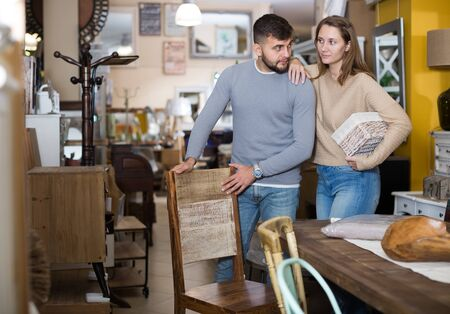 Loving couple looking for wooden chairs in shop of secondhand furniture