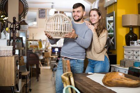 Loving couple looking for stylish hanging lamp in shop of secondhand furniture Stock Photo