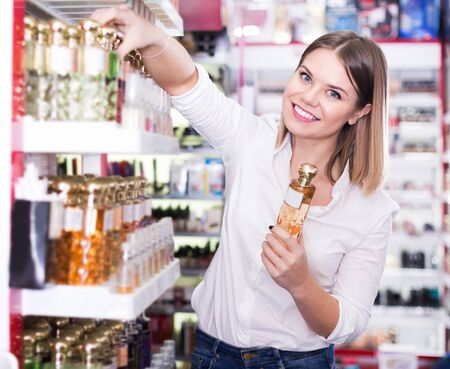 Young cheerful woman looking for stylish fragrance of perfume in cosmetic shop Фото со стока