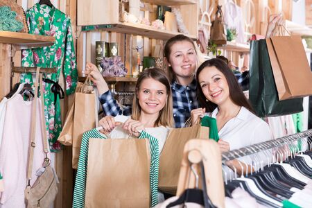 Smiling young women  friends carrying paper bags and clothes  in fashion store