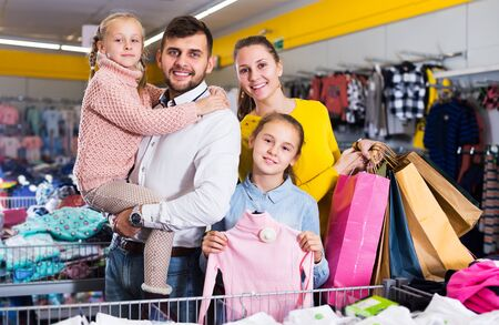 Young cheerful family with two daughters after shopping in clothes store