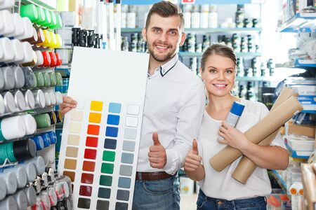 male and female select colors of paint on the palette in the paint store