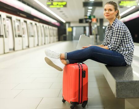 Pretty girl traveler waiting for train at metro station sitting on stone bench with legs stretched out on suitcase
