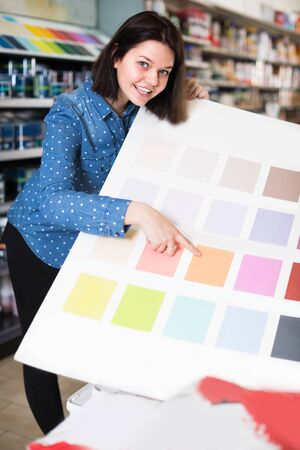 Young female is deciding on best color scheme in paint supplies store. 写真素材