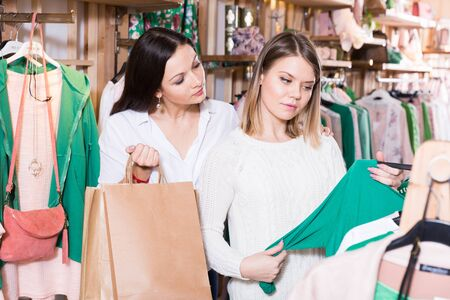 Positive young women friends choosing green pullover in the fashion store 写真素材