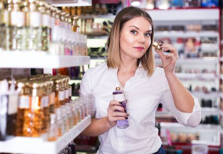 Young positive woman looking for stylish fragrance of perfume in cosmetic shop Фото со стока