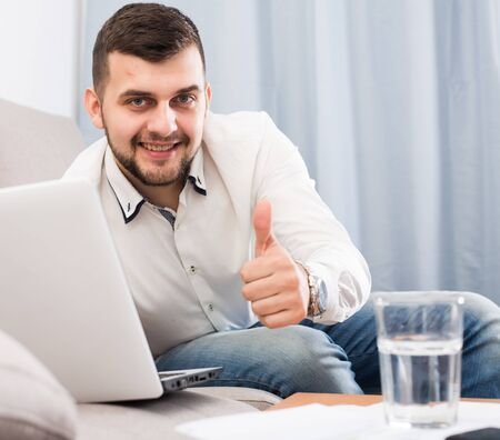 Young man using laptop to book hotel online at home