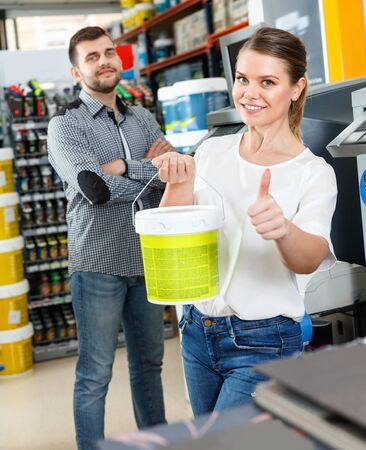 Young pleasant woman standing near man and holding bucket of paint in household store