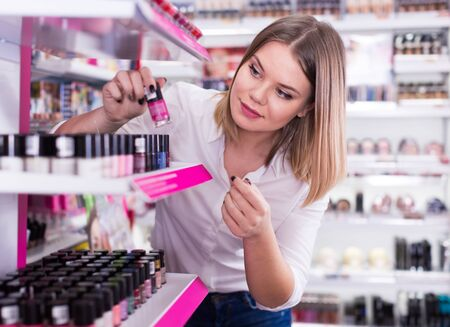 Smiling girl shopping in cosmetics store, choosing new nail polishes