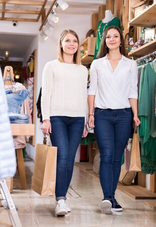 Smiling young women  carrying  paper bags with purchases  in fashion store 写真素材