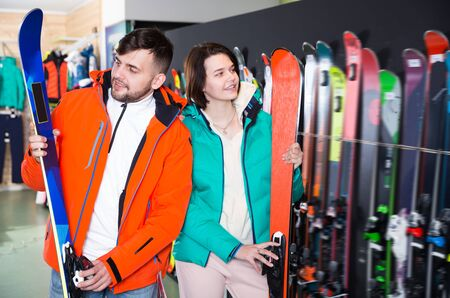 Portrait of smiling man and woman buying skis in store Stock fotó