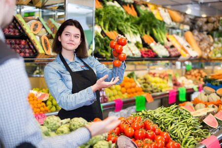 Smiling female seller assisting customer to buy tomatoes in grocery shop