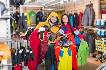 Young loving couple demonstrating the tourist equipment in a sports clothes store. Focus on man