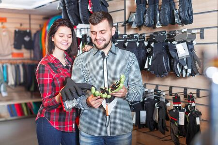 Happy loving couple deciding on protective gloves in sports clothes store