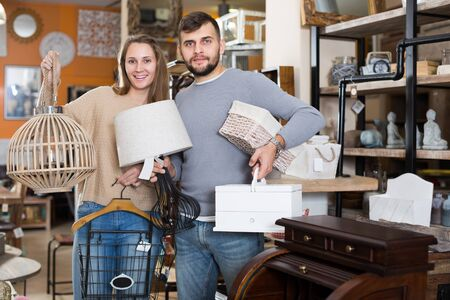 Portrait of happy young pair standing with purchases in furnishings showroom 写真素材