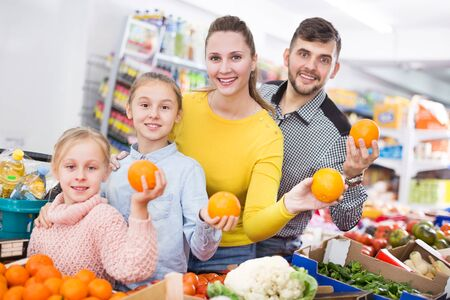 Young family of four shopping together at greengrocery store choosing oranges 写真素材