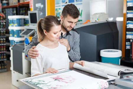 Young couple looking samples of wallpaper at magazine in household shop Imagens
