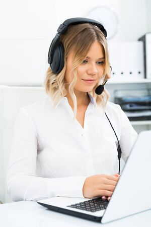 Young girl in call center with headphones sitting with laptop Banco de Imagens