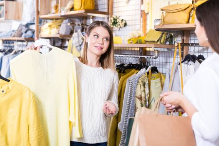 Young female assistant demonstration fashion yellow  pullover to woman in boutique