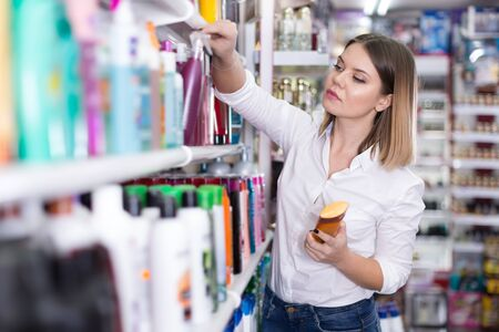 Young concentrated woman looking for haircare cosmetics at the shop Фото со стока