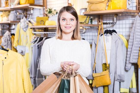 Young woman  carrying  paper bags with purchases  in fashion store