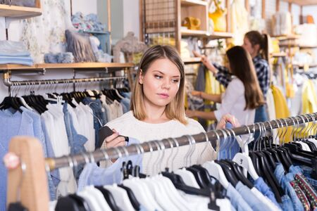 Portrait of young woman customer looking  blue shirt  in the showroom 写真素材